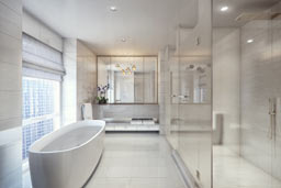 bathroom of an apartment with mirrors along one wall and a bath tub under a window on the other wall